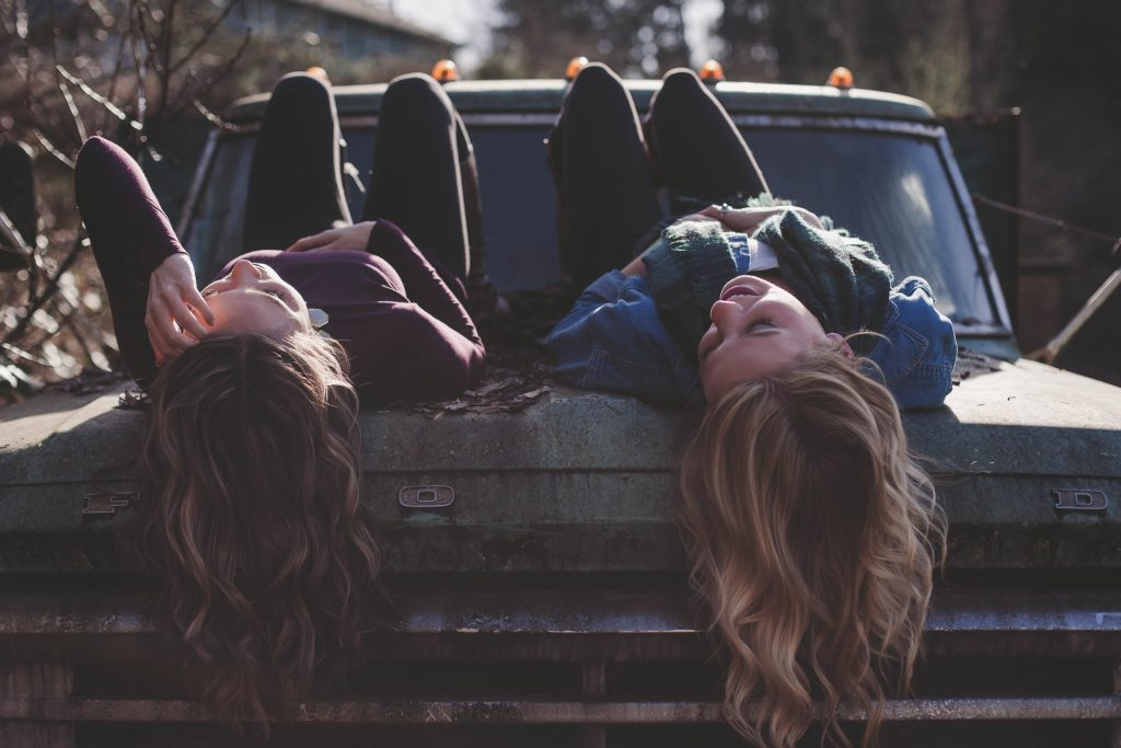 Girls talking on the bonnet off an old car